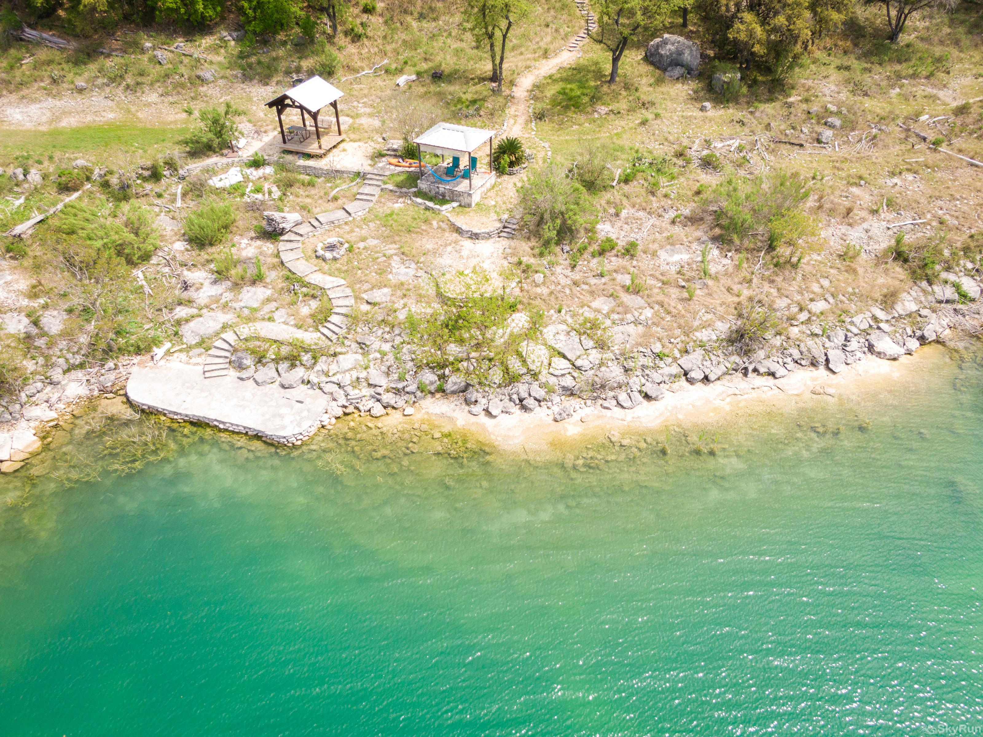 LAKESIDE VILLA Aerial view of the shoreline and gazebo below the home
