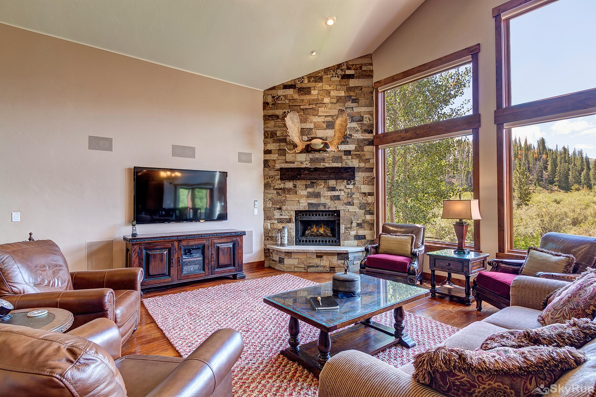 Swan River Retreat LIving room with floor-to-ceiling stone fireplace