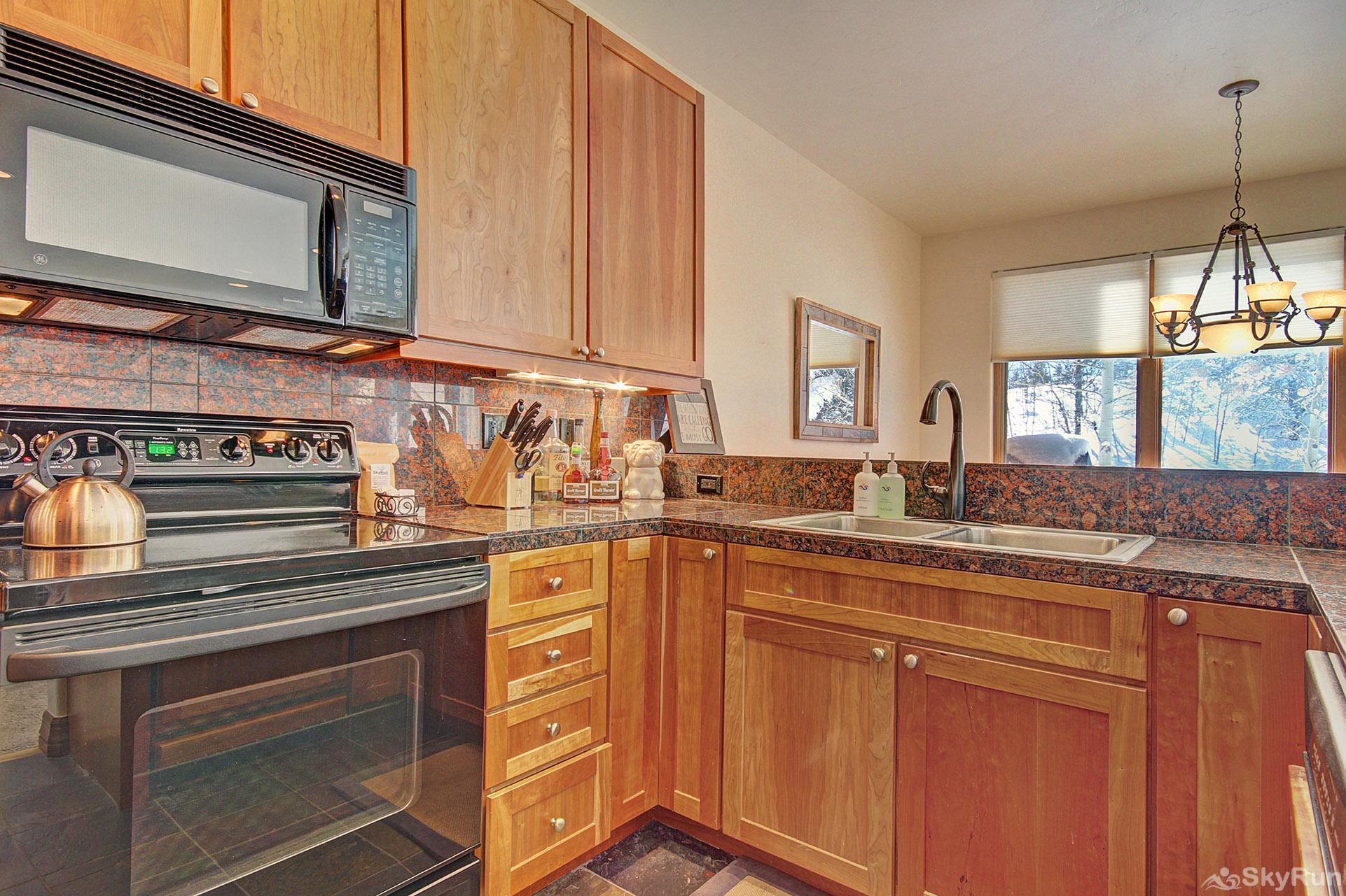 Highland Greens Pine Modern kitchen features full size stove, fridge and dishwasher