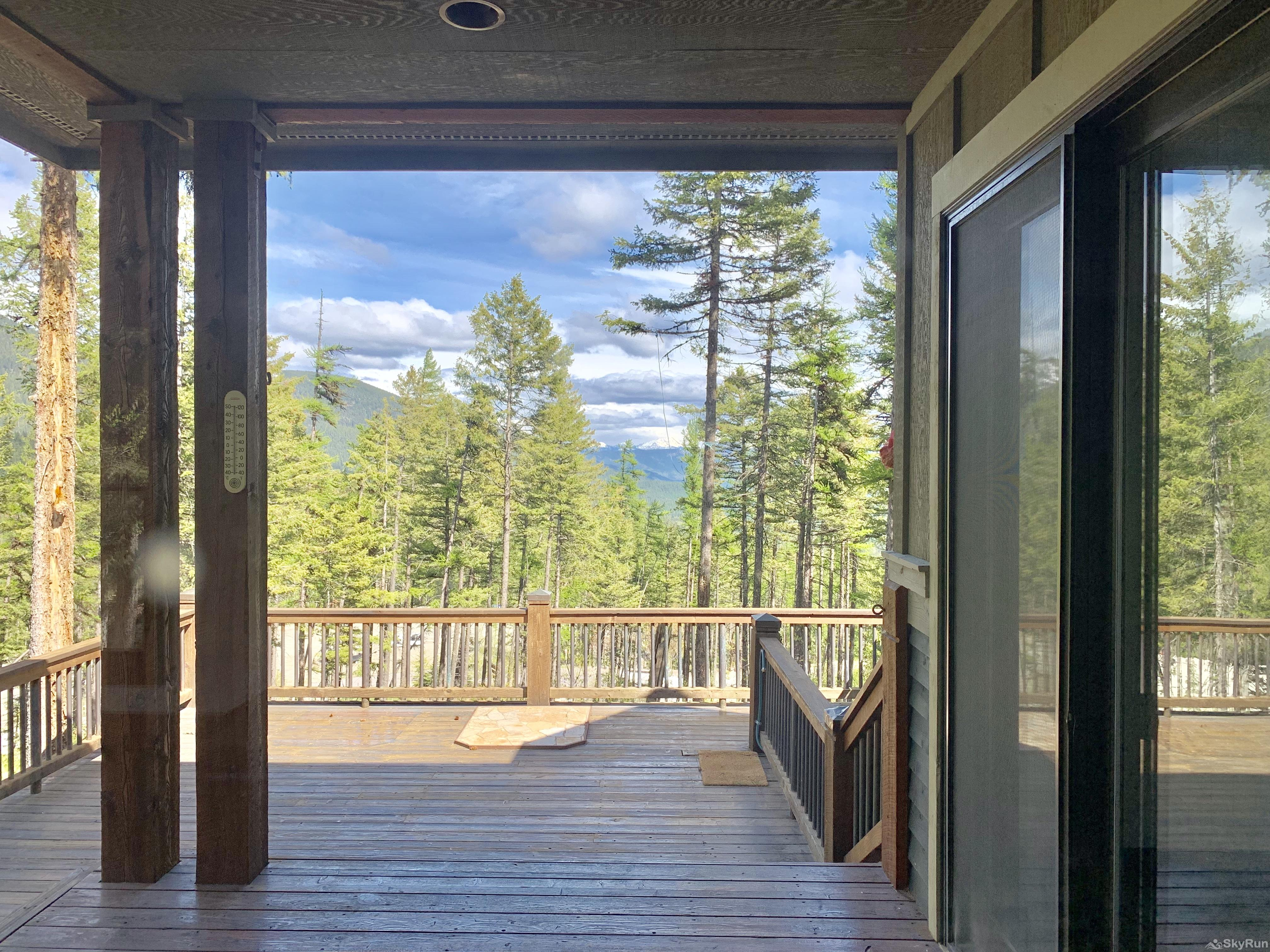 Whispering Pines Chalet A spacious deck that is partially covered with views of the mountains.