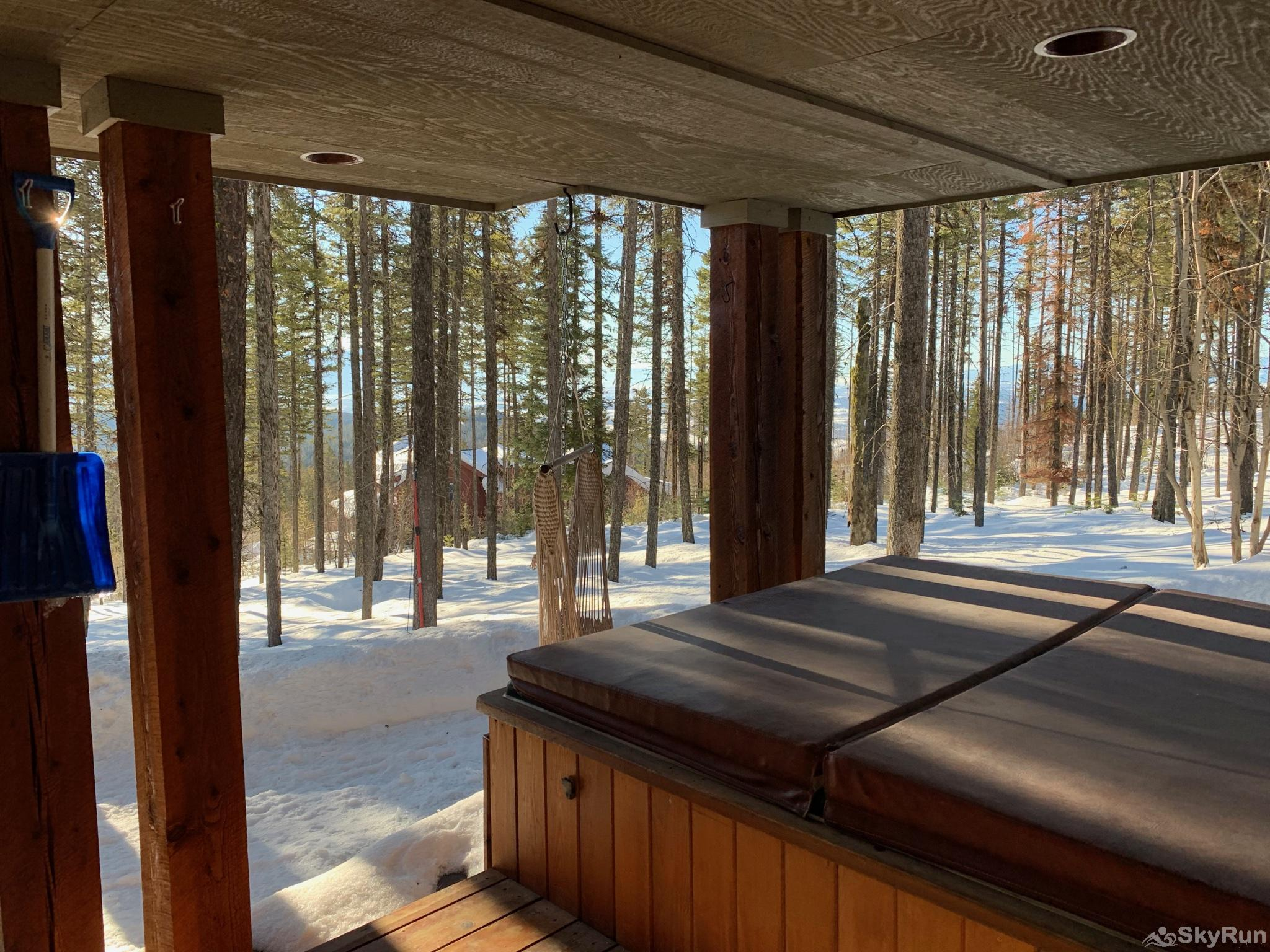 Whispering Pines Chalet The hot tub is protected from the snow but has great views of the surrounding trees.