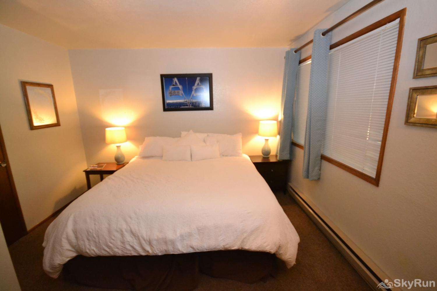 Ptarmigan Village 86 Second bedroom with King sized bed and a door to an outside deck