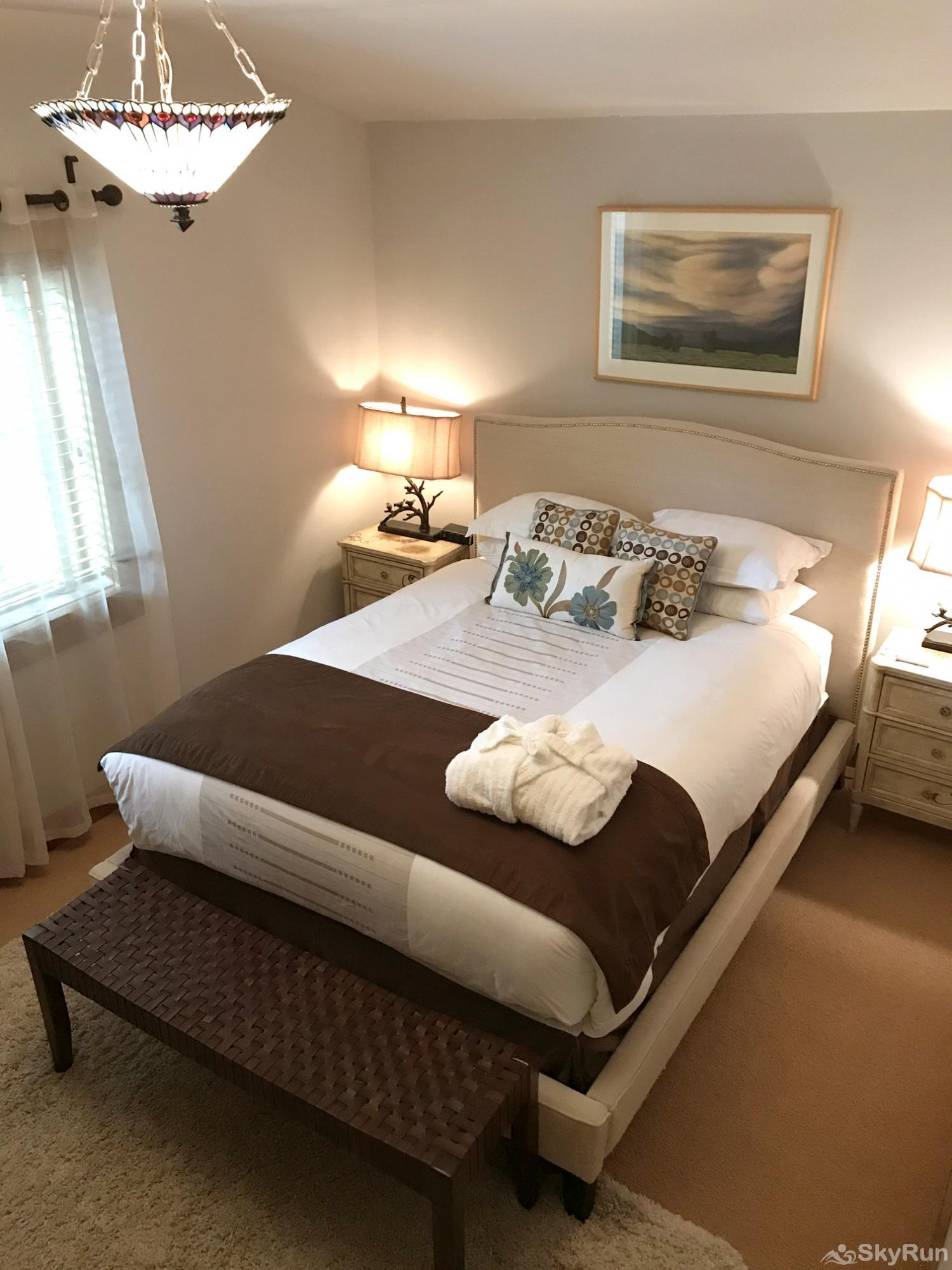 Whitefish River Inn The Robin bedroom has an upholstered queen bed, dresser, bedside tables, and a closet.